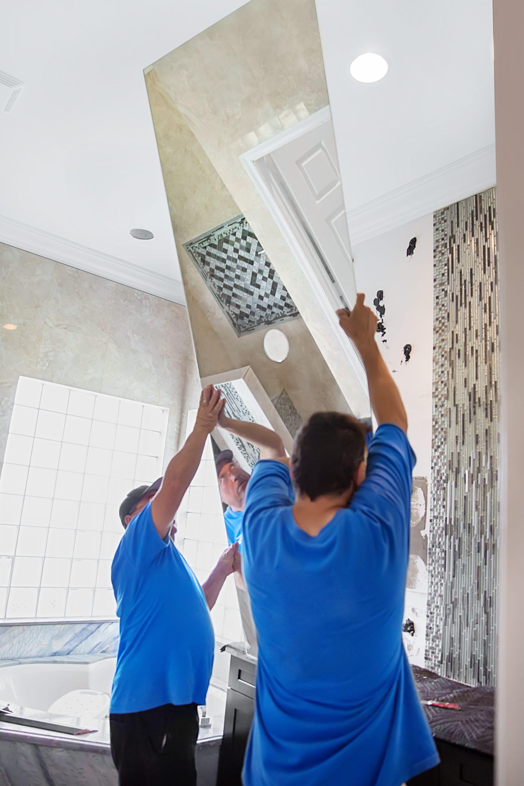 Workers installing bathroom mirror