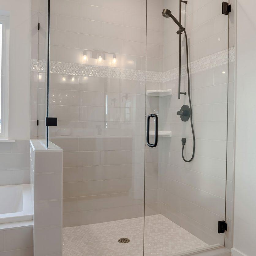 Bathroom shower stall with half glass enclosure adjacent to built in bathtub